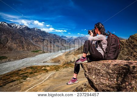 Dhankar gompa. Spiti Valley, Himachal Pradesh, India. Nature photographer tourist with camera shoots while standing on top of the mountain.