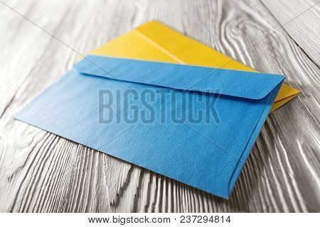 two yellow and blue envelopes with letters on white wooden background.  Blanks for the designer. Con