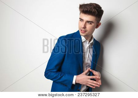 portrait of pensive young casual man looking to side while standing with fingers together and leaning against a grey wall