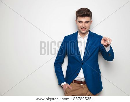 smart casual man with hand in pocket pointing finger while standing and leaning against a white wall, relaxed.