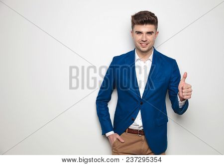 happy and relaxed smart casual man makes ok sign while standing against a white wall, wearing a blue suit jacket and a pair of brown pants