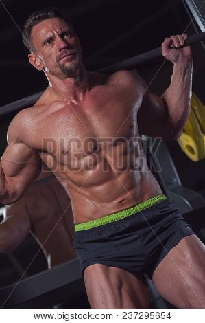 Portrait Of A Handsome Strong Male Athlete Exercising In The Gym With A Barbell. Sports Concept
