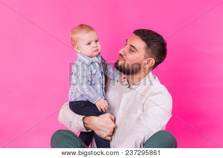 Happy Father With His Baby Son On Pink Background.
