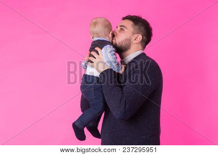 Happy Portrait Of The Father And Son On Pink Background. In Studio.