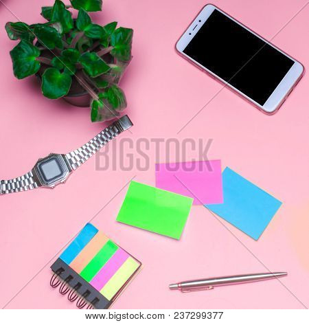 Working Space With A Clock, Telephone, Stickers, Notes On A Pink Background. Place For Text. The Wor