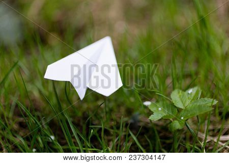 Moscow, Russia - April 22, 2018: A Paper Airplane Lies On The Grass. Action To Launch Aircraft In Su