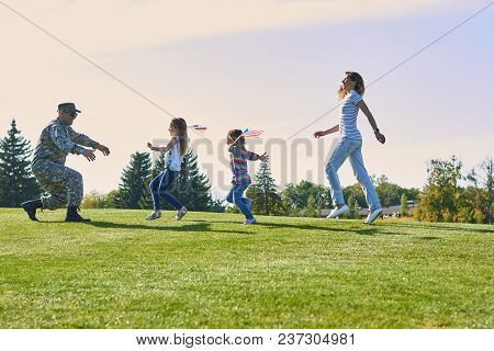 Soldier Is Reuniting With His Family Outdoor. Father Is Meeting His Wife And Two Daughters, Side Vie
