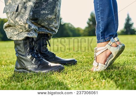Feet Of Soldier An Little Girl Outdoors. Soldier Feet With Boots And Little Daughter With Sandals. L