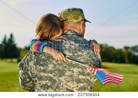 Little Girl Is Hugging His Fathger Us Soldier. Daughter With American Flag Is Embracing Her Daddy In