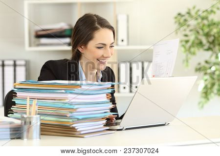 Competent Executive Working Hard Online With A Laptop And A Lot Of Paperwork At Office