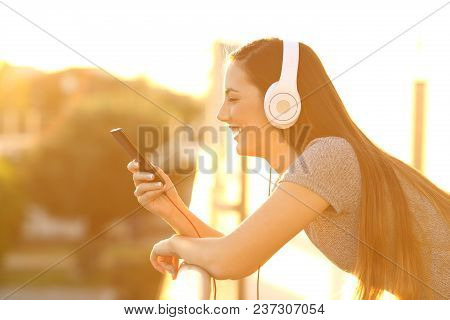 Side View Of A Happy Girl Listening To Music At Sunset In A Balcony