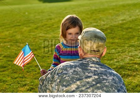 Daughter With American Flag And Her Daddy. Love Concept Of Soldier And Little Girl Outdoors.