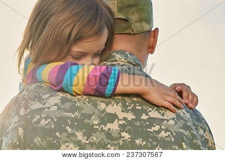 Little Female Child Is Hugging A Soldier. Close Up Portrait Of Happy Girl Is Hugging Her Father In M