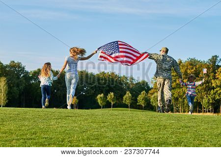 Back View, Patriotic Family Moving With Huge American Flag. People Running On The Grass.