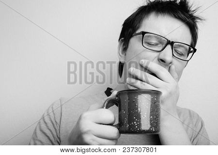 Sleepy Yawning Man In Eyeglasses With Red Cup Of Tea Or Coffee Has Uncombed Hair In Underwear On Lig