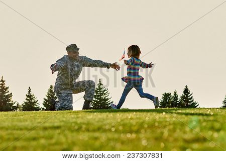 American Soldier Meet His Daughter Outdoor. Little Girl With Usa Flag Is Running To Her Father In Mi