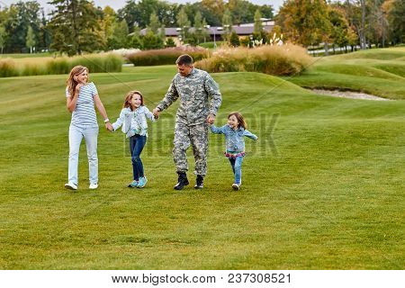 Soldier Walking With Kids And Wife. Holding Hands, Happy Reunion Of Father And His Family. Walk On T