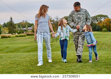 Happy Family With Soldier Father Walking Outdoor. Front View, Man In Military Uniform With His Wife