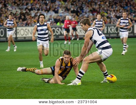 MELBOURNE - SEPTEMBER 9 : Sam Mitchel (C) scops the ball out during Geelong's win over Hawthorn - September 9, 2011 in Melbourne, Australia.