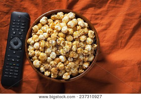 Wooden Bowl With Sweet Popcorn And Tv Remote On Orange Bedding. Top View. Snacks And Food For A Movi