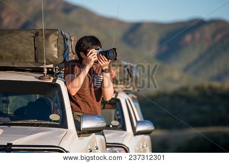 Young Asian Man Traveler And Photographer Sitting On The Car Window Photographing Sunrise During Roa