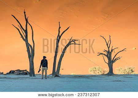 Young Man Photographer And Traveler Standing Between Dead Trees In Deadvlei (sossusvlei) During Sunr