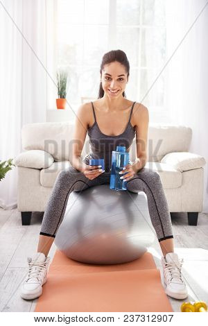 Useful And Convenient. Charming Upbeat Woman Sitting On The Fitness Ball And Posing For The Camera W