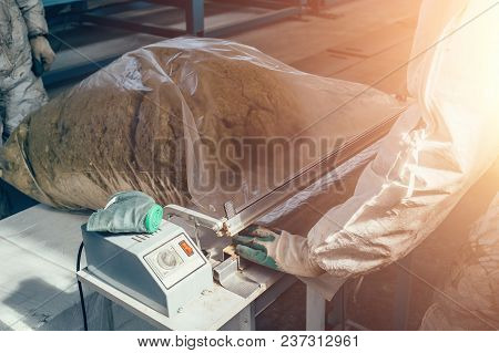 Worker Packs Waste Products Into Plastic Bags At Factory, Close Up, Toned