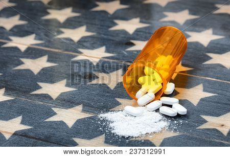 Front View Of Prescription Bottle Filled With Generic Opioid Pain Killer Tablets On Rustic Usa Flag