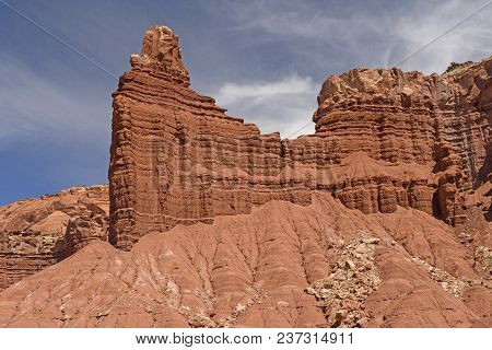 Rock Cliffs Emerging Out Of The Sand In Capitol Reef National Park In Utah