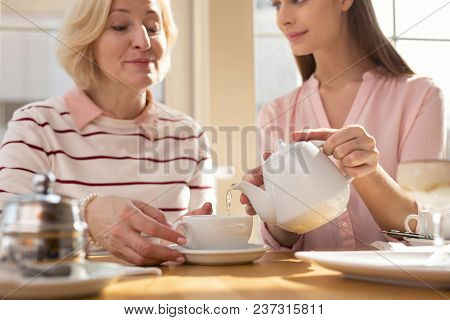 I Love You. Charming Content Girl Pouring Tea While Having Lunch With Her Granny In A Cafe