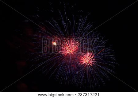 A Red And Blue Fireworks Exploding In The Night Sky