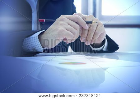 Partially Closeup Of Businessman Hand Holding A Pencil Attending A Conference Or Meeting With Attent