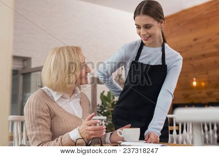 Good Cafe. Alert Young Waitress Smiling And Serving Coffee For Her