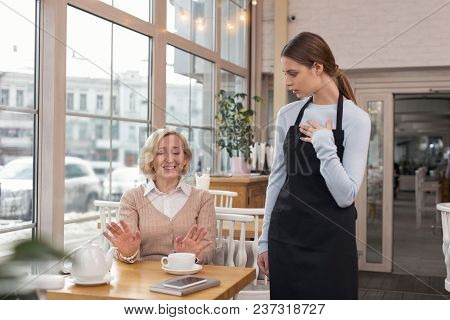 I Am Sorry. Kind-hearted Aged Woman Talking To The Waitress And Telling That Is Not Her Order