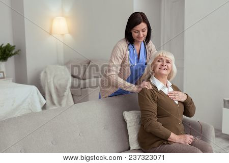Excellent Massage. Attractive Nurse Proposing Massage To Nice Elder Woman Who Sitting On Sofa