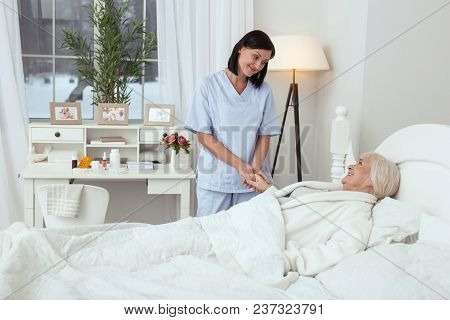 Be Careful. Cheerful Gay Nurse Taking Elder Woman And Who Lying In Bed