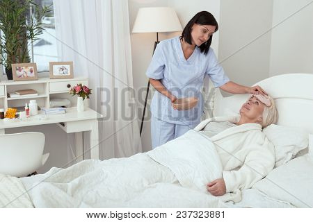 Cold Compress. Attractive Concentrated Nurse Applying Compress While Elder Woman Smiling In Bed