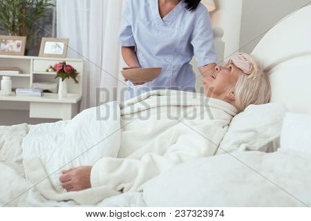 Struggle With Fever. Nurse Applying Compress While Inspired Elder Woman Grinning In Bed