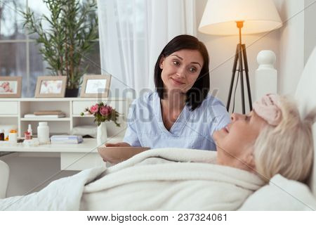 No Pain. Positive Experienced Nurse Applying Compress While Elder Woman Posing In Bed