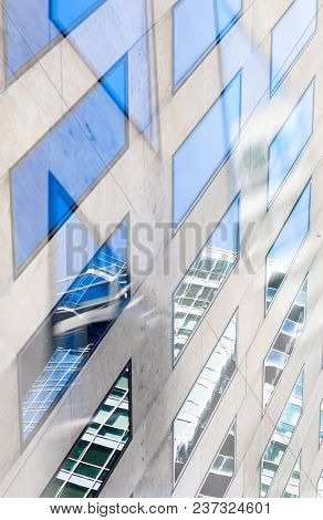 Double exposure architectural abstract. Detail of windows and reflections with focus on reflected buildings.