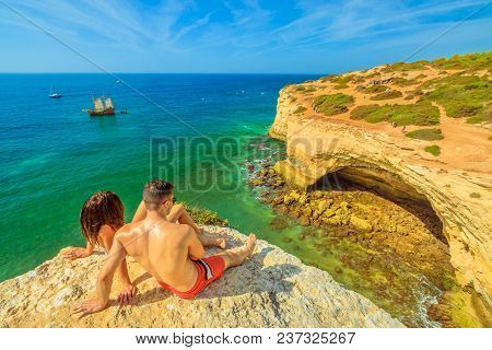 Benagil, Portugal - August 23, 2017: Lifestyle Couple In Summer Holidays, Sunbathing On Cliffs In Al