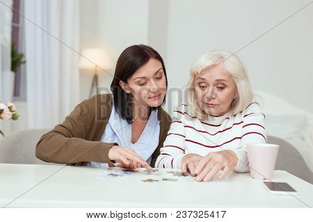 Pleasant Time Spending. Jolly Elder Woman And Caregiver Sitting While Gathering Puzzle