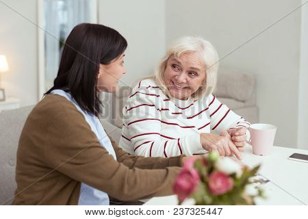 Happy Time. Jovial Elder Woman And Caregiver Talking While Gathering Puzzle