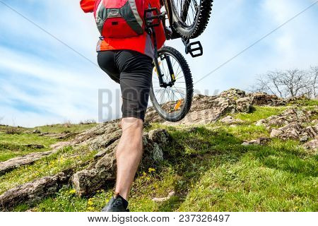 Enduro Cyclist Taking his Mountain Bike up to the Beautiful Rocky Trail. Extreme Sport and Adventure Concept. Free Space for Text.