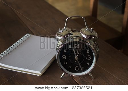 Retro Alarm Clock With Blank Realistic Spiral Notepad Notebook On Wooden Table, Stock Photo