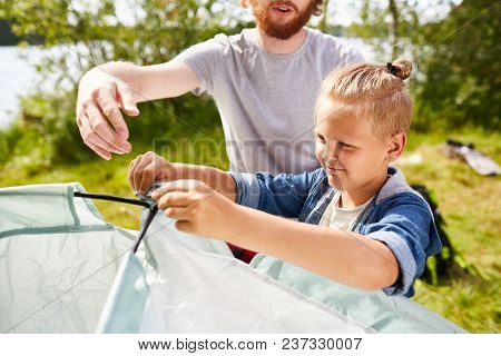 Two boy scouts making their tent for living in natural environment during backpack trip