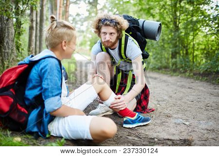 One of boy scouts taking care of his buddy with injured leg while sitting on forest path on their way to camp