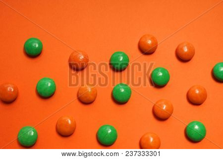 Colored candy on a orange background. Green and orange candy.