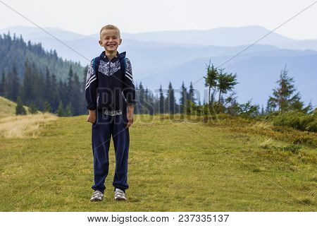 Little Boy With A Backpack Hiking In Scenic Summer Green Carpathian Mountains. Child Standing Alone